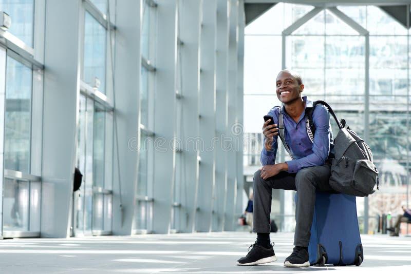 Hombre de negocios sonriente que se sienta en el equipaje en el aeropuerto con el teléfono celular imagen de archivo libre de regalías