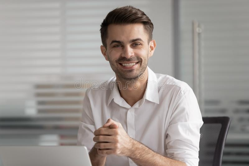 Hombre de negocios sonriente que se sienta en el escritorio con el ordenador portátil que mira la cámara imagen de archivo