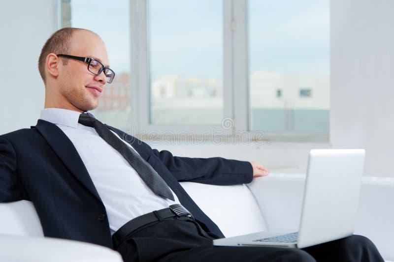 Hombre de negocios sonriente que se sienta en el sofá con el ordenador portátil foto de archivo