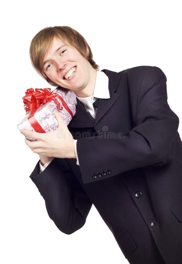 Hombre de negocios sonriente que se sostiene presente con la cinta imagen de archivo