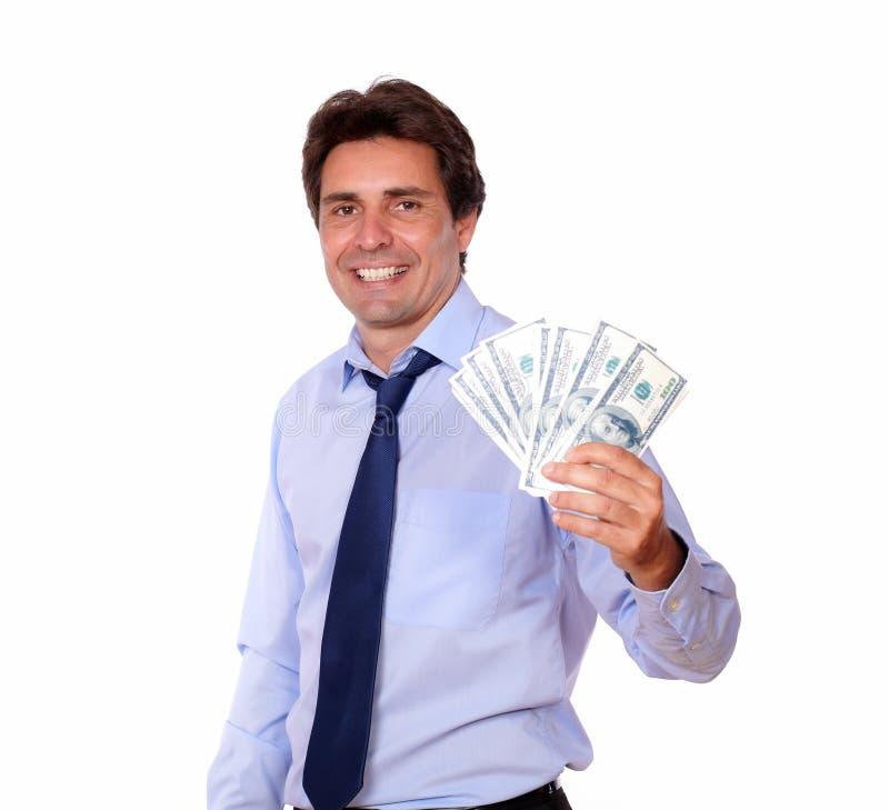 Hombre de negocios sonriente que soporta el dinero del efectivo fotografía de archivo