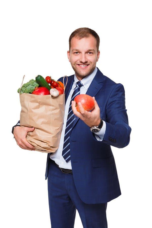 Hombre de negocios sonriente que sostiene el panier lleno de verduras aisladas en el fondo blanco imagen de archivo
