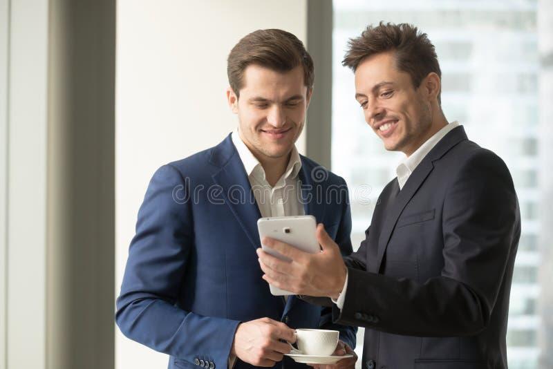 Hombre de negocios sonriente que sostiene la tableta digital que muestra a algo la diversión foto de archivo libre de regalías