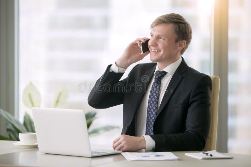 Hombre de negocios sonriente que tiene phonetalk foto de archivo libre de regalías
