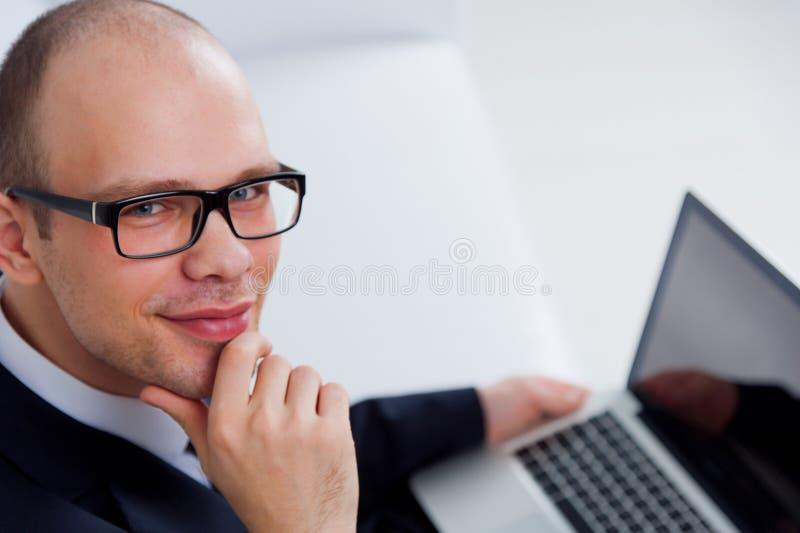 Hombre de negocios sonriente que trabaja con el ordenador portátil imágenes de archivo libres de regalías