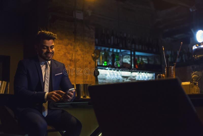 Hombre de negocios sonriente usando smartphone en la barra imagen de archivo