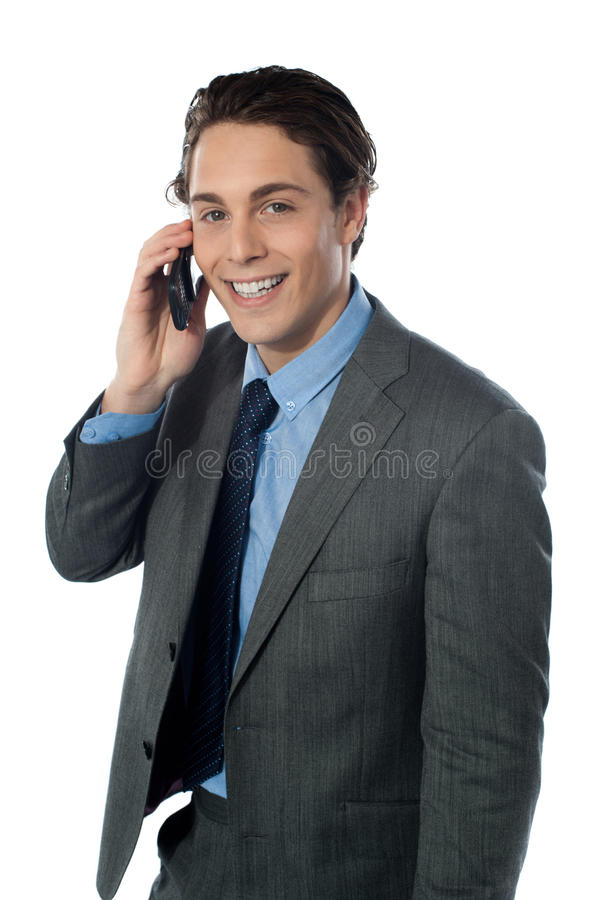 Hombre de negocios sonriente usando un teléfono celular foto de archivo libre de regalías
