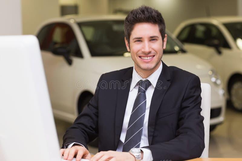 Hombre de negocios sonriente usando una computadora portátil imagen de archivo