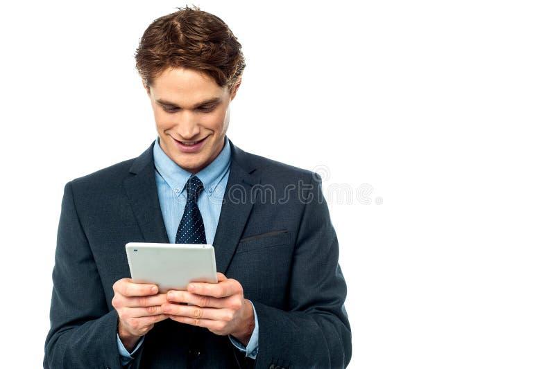 Hombre de negocios sonriente usando una PC de la tableta foto de archivo libre de regalías