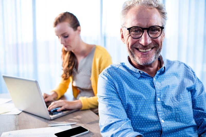 Hombre de negocios sonriente y empresaria concentrada fotografía de archivo libre de regalías
