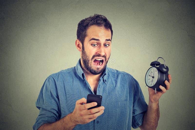 Hombre de negocios sorprendido con el despertador que mira el teléfono elegante imagen de archivo libre de regalías