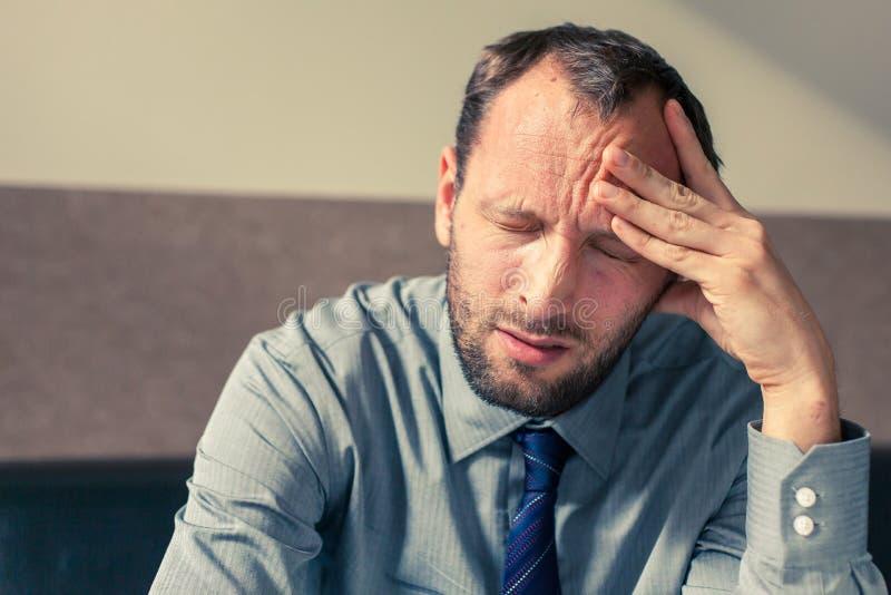 Hombre de negocios subrayado que consigue un dolor de cabeza en casa en el ro vivo foto de archivo