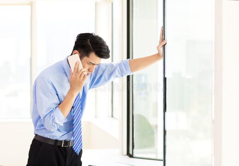 Hombre de negocios subrayado que habla en el teléfono en oficina fotos de archivo libres de regalías