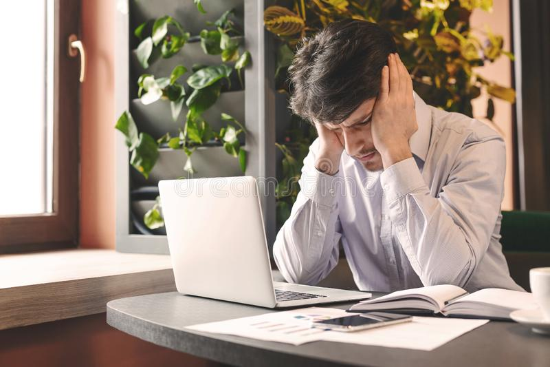 Hombre de negocios subrayado que se sienta delante del ordenador port?til en caf? fotos de archivo libres de regalías