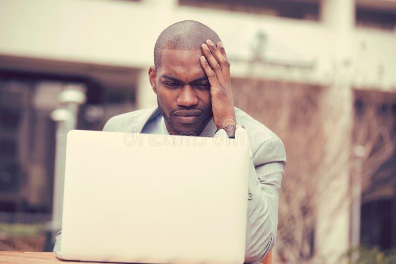 Hombre de negocios subrayado que se sienta fuera de la oficina corporativa que trabaja en el ordenador portátil imagenes de archivo