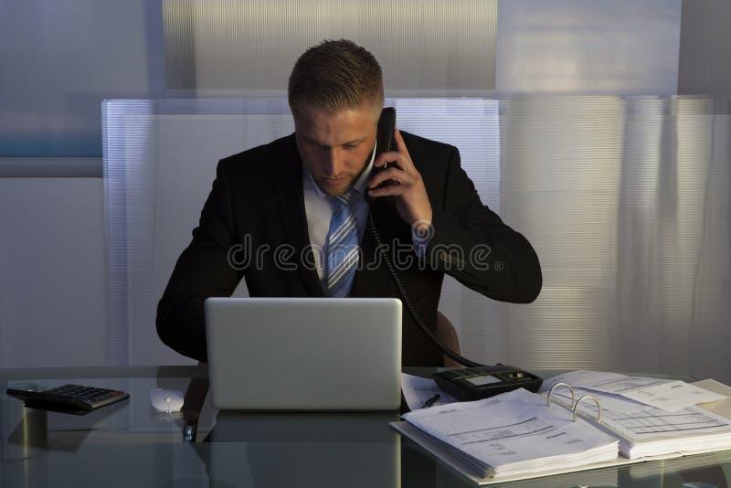 Hombre de negocios subrayado que trabaja tarde en la noche fotos de archivo