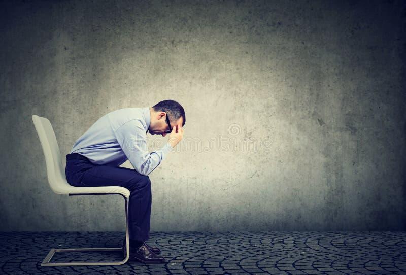 Hombre de negocios subrayado triste que se sienta en una oficina vacía fotos de archivo