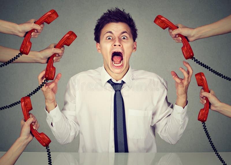 Hombre de negocios subrayado y nervioso a muchas llamadas del trabajo que gritan en la desesperación foto de archivo