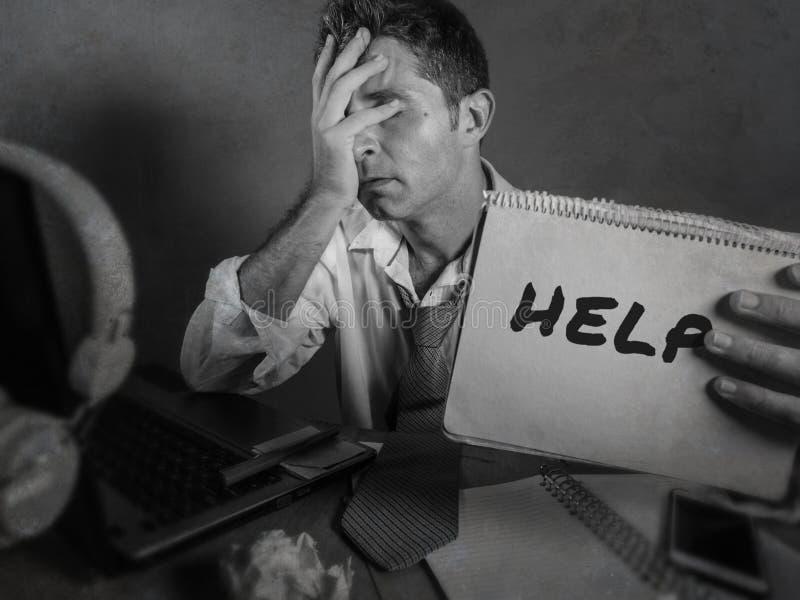 Hombre de negocios sucio y deprimido joven que muestra la libreta que pide la ayuda desesperada y triste en el escritorio del ord imagenes de archivo