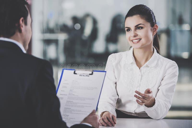 Hombre de negocios Taking Resume de la mujer en oficina imagen de archivo libre de regalías