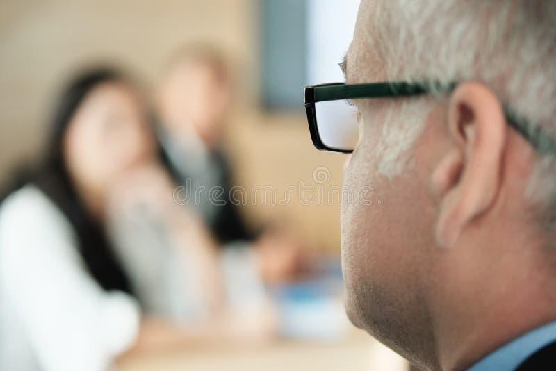 Hombre de negocios Talking To Colleagues y clientes en sala de reunión de la oficina imagen de archivo libre de regalías