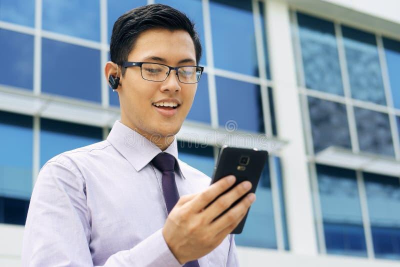 Hombre de negocios Talking Video Call en móvil con Bluetooth Handsfre fotografía de archivo libre de regalías