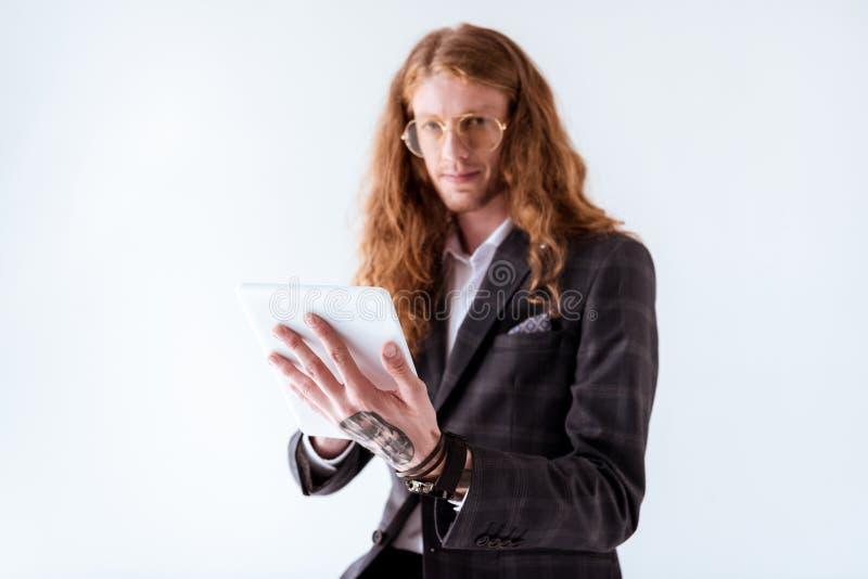 hombre de negocios tatuado elegante con la tableta de la tenencia del pelo rizado foto de archivo libre de regalías