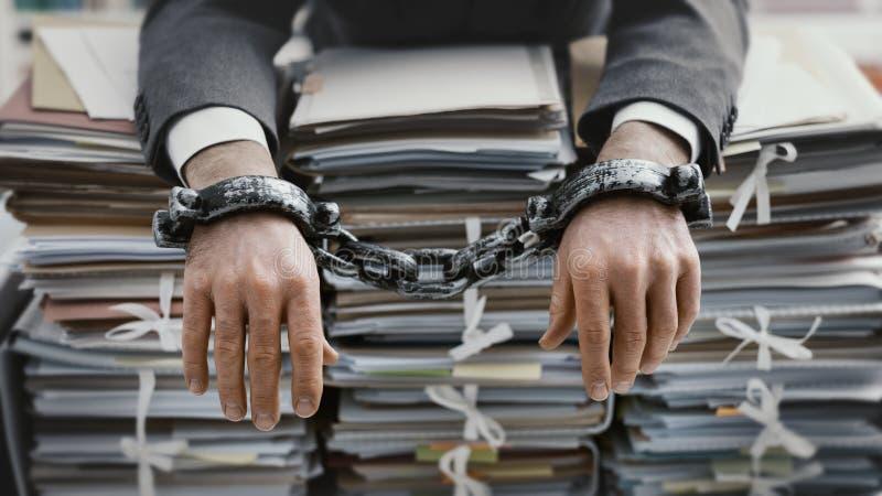 Hombre de negocios trabajado demasiado encadenado al lugar de trabajo imagenes de archivo