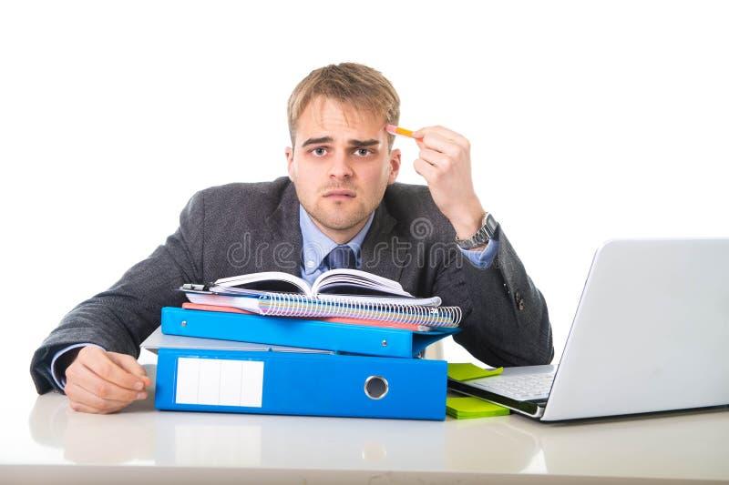 Hombre de negocios trabajado demasiado y abrumado de los jóvenes en la tensión que se inclina en la carpeta de la oficina agotada fotografía de archivo libre de regalías