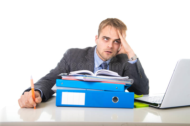 Hombre de negocios trabajado demasiado y abrumado de los jóvenes en la tensión que se inclina en la carpeta de la oficina agotada imagen de archivo