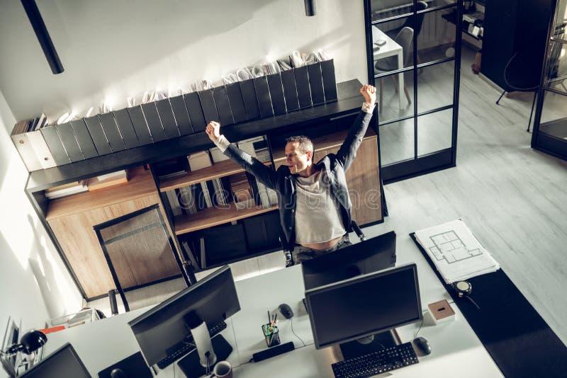 Hombre de negocios trabajador que estira el suyo detrás después de trabajar demasiado de largo imágenes de archivo libres de regalías