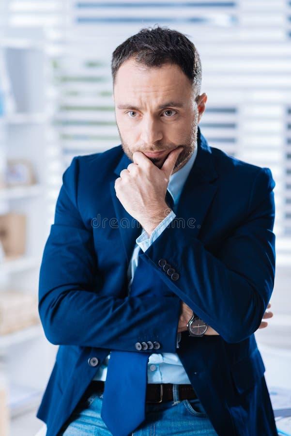 Hombre de negocios tranquilo elegante que toca su cara mientras que piensa en la situación foto de archivo