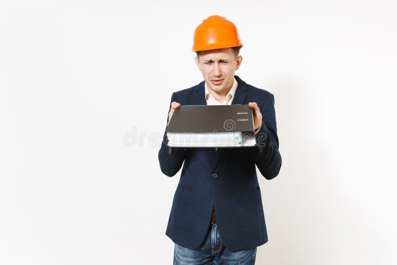 Hombre de negocios trastornado descontento en el traje oscuro, casco protector de la construcción que sostiene la carpeta negra p foto de archivo