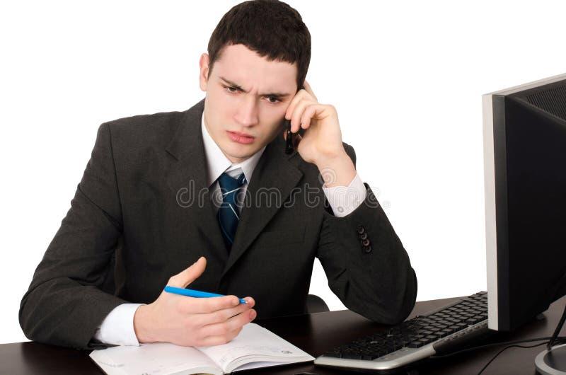 Hombre de negocios que se sienta en el escritorio que habla en el teléfono. imagen de archivo