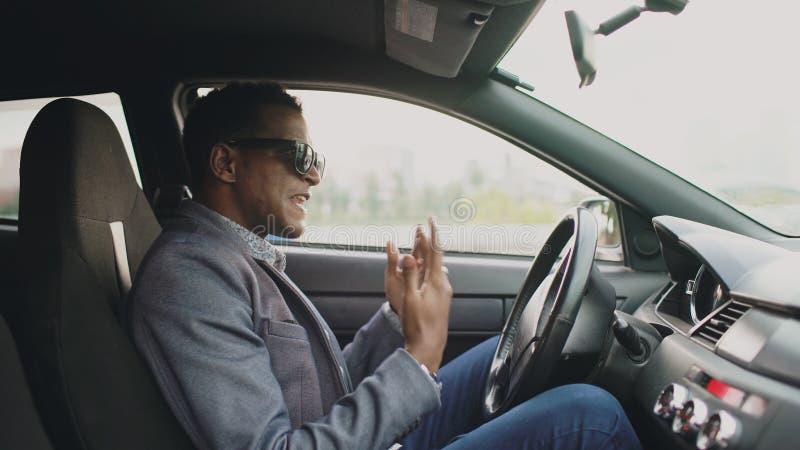 Hombre de negocios trastornado y enojado de la raza mixta que se sienta dentro de su coche al aire libre imagenes de archivo