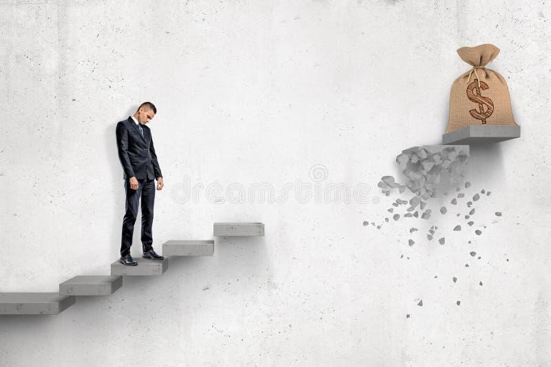 Hombre de negocios triste que mira abajo en escalera concreta gris con el bolso grande del dinero en la cima de él pero con la pa foto de archivo libre de regalías