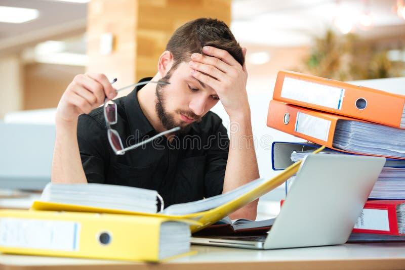 Hombre de negocios triste que se sienta en la tabla con muchas carpetas imagenes de archivo