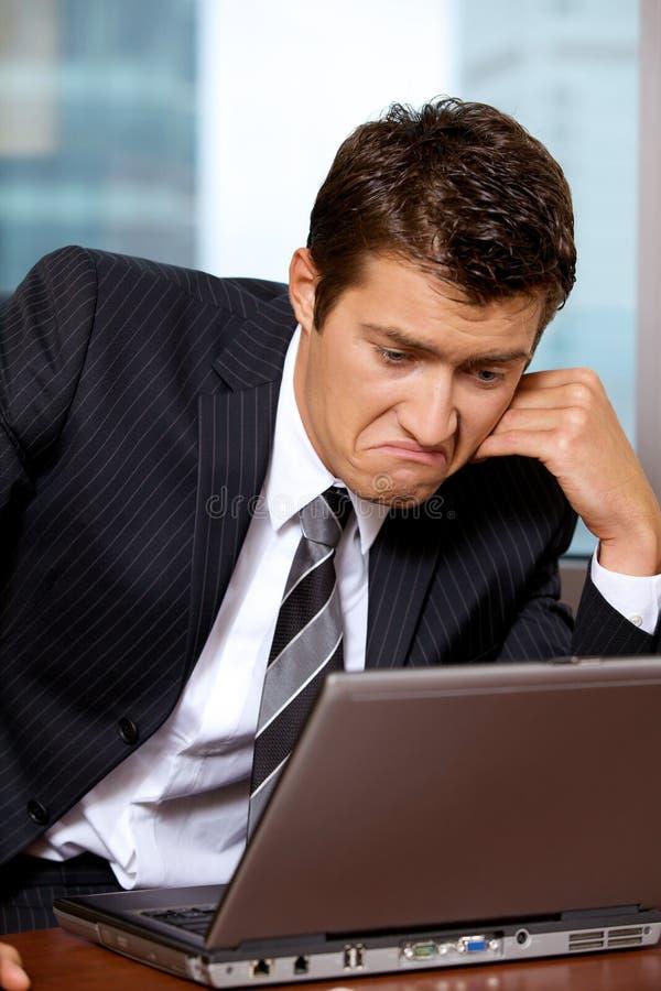 Hombre de negocios triste usando el ordenador portátil en oficina fotos de archivo