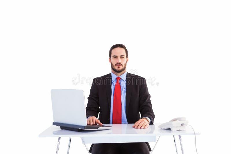 Hombre de negocios Unsmiling que se sienta en el escritorio foto de archivo