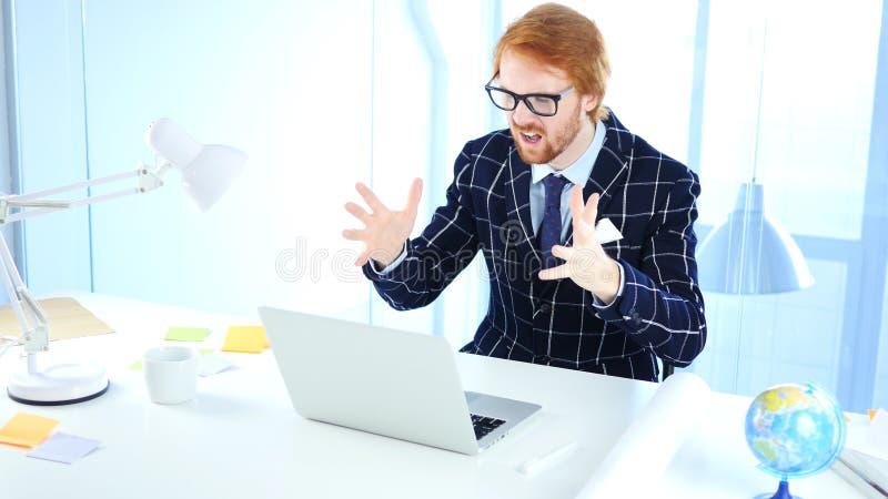 Hombre de negocios Upset del pelirrojo por pérdida mientras que trabaja en el ordenador portátil, diseñador creativo fotos de archivo
