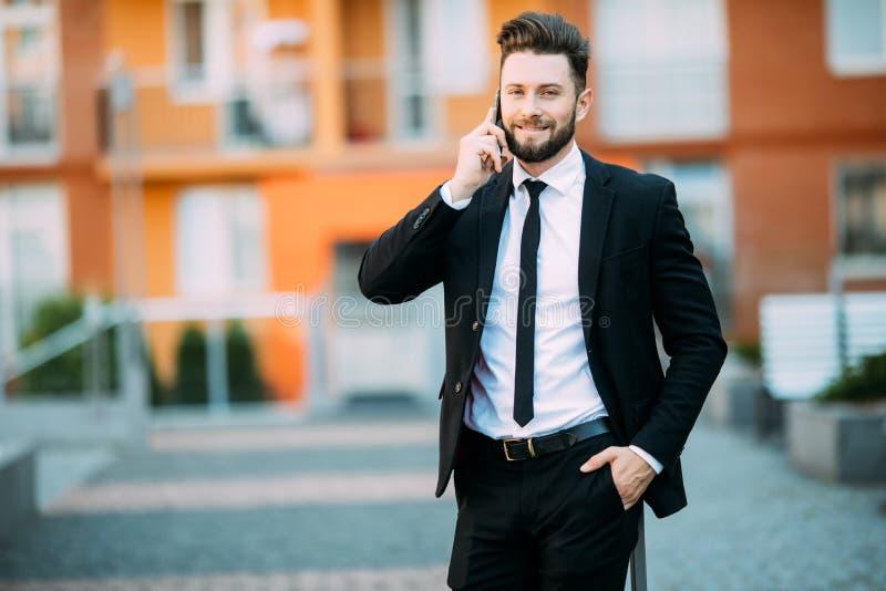 Hombre de negocios urbano joven en el teléfono elegante que corre en calle que habla en smartphone al aire libre foto de archivo libre de regalías