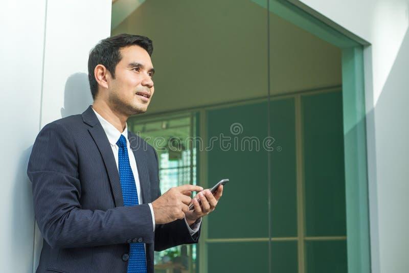 Hombre de negocios usando el edificio de oficinas del indise del teléfono móvil con smili imagen de archivo