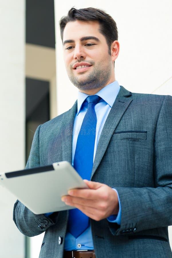 Hombre de negocios usando el ordenador de la tablilla imagen de archivo