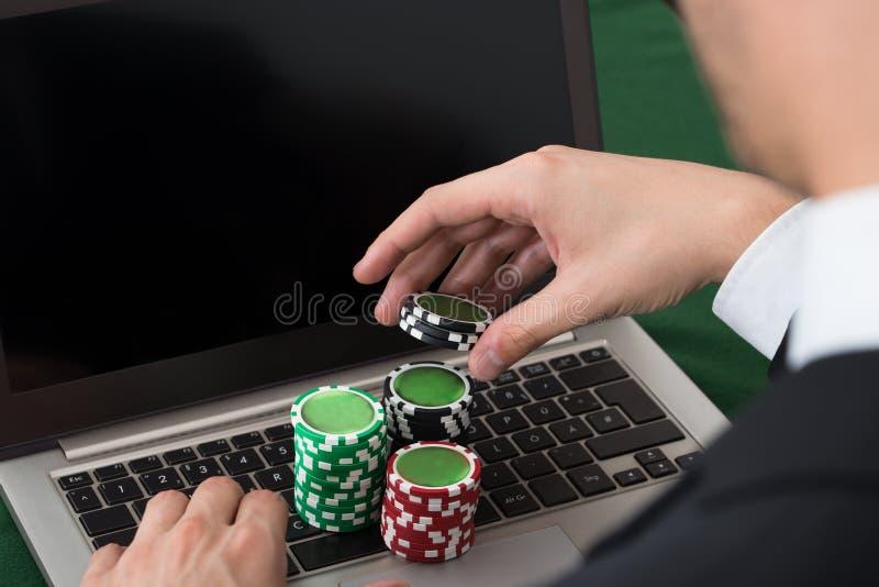 Hombre de negocios usando el ordenador portátil con las fichas de póker apiladas imagen de archivo
