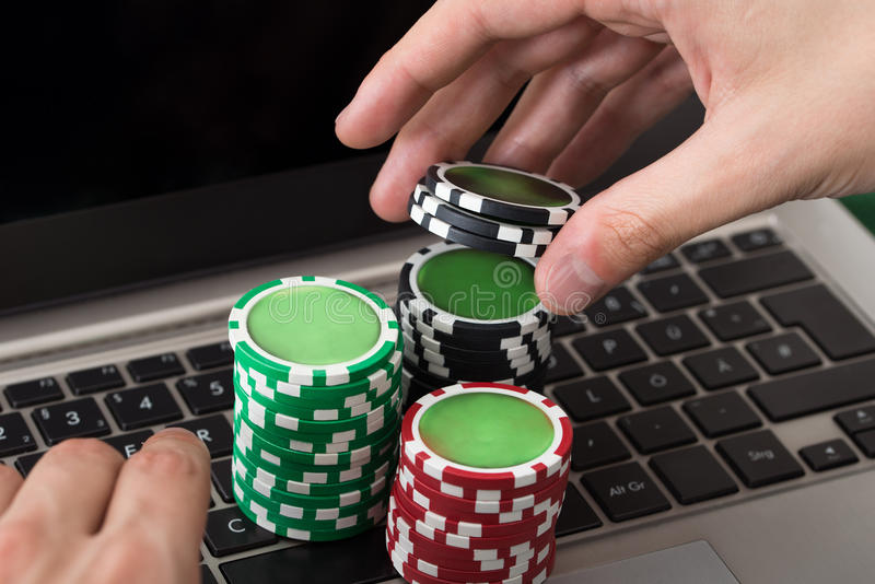 Hombre de negocios usando el ordenador portátil con las fichas de póker apiladas fotos de archivo