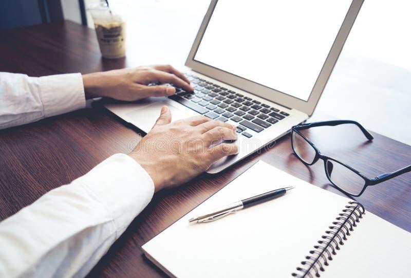 Hombre de negocios usando el ordenador portátil del ordenador con la pantalla en blanco en tienda del café fotografía de archivo