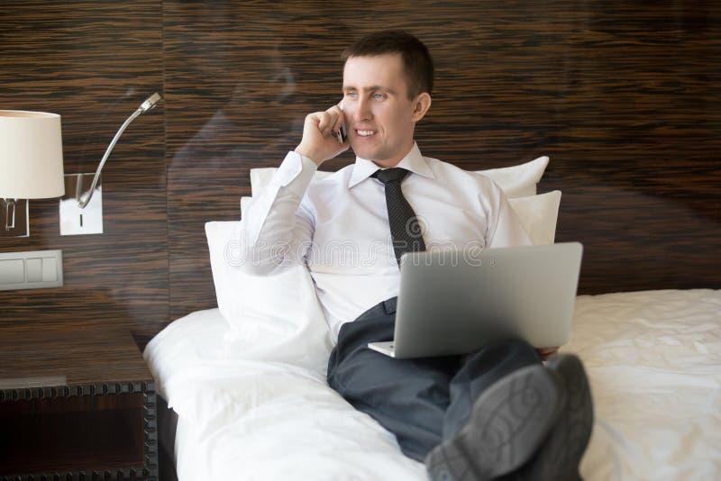 Hombre de negocios usando el ordenador portátil en hotel imagen de archivo