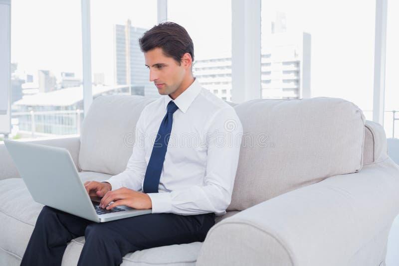 Hombre de negocios usando el ordenador portátil en un sofá foto de archivo libre de regalías
