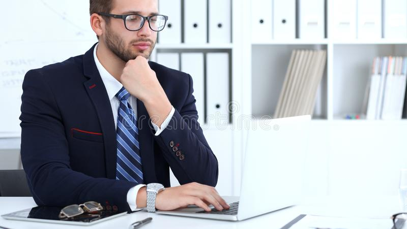 Hombre de negocios usando el ordenador portátil mientras que se sienta en el escritorio en oficina Foco en llevar barbudo sonrien fotografía de archivo libre de regalías