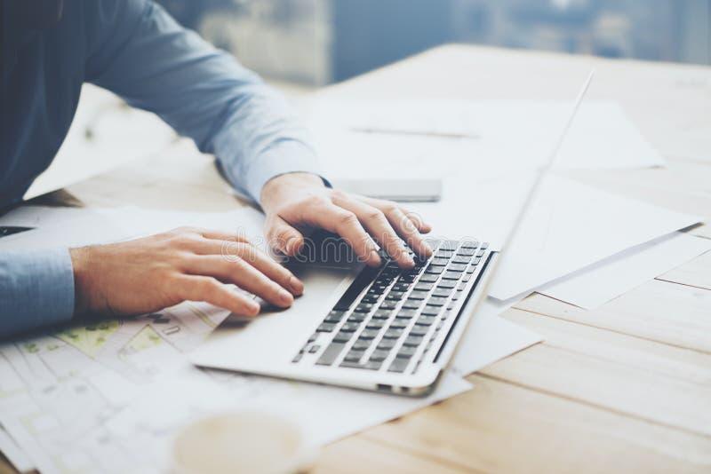 Hombre de negocios usando el ordenador portátil para el nuevo proyecto arquitectónico Cuaderno genérico del diseño en la tabla Fo fotografía de archivo